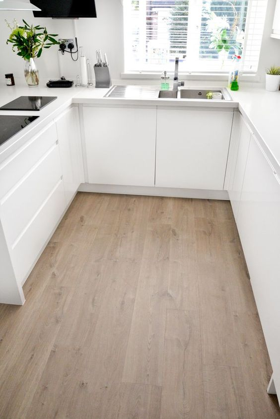 a minimalist white kitchen with a neutral laminate floor, black appliances and sleek surfaces is a very chic space