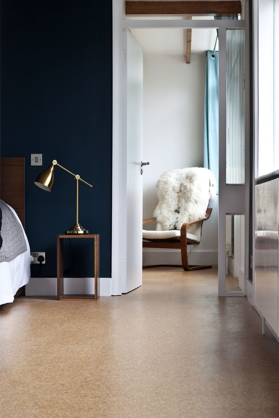 a modern bedroom with navy walls, a cork floor, chic furniture and touches of brass is an amazing space