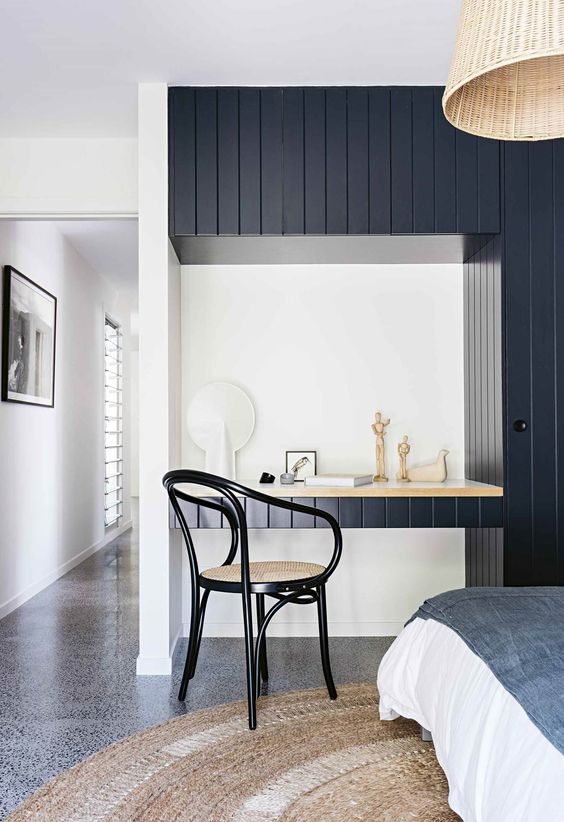 a modern coastal home office nook with a navy beadboard wall, a built-in desk, a chic rattan chair and a rattan lamp