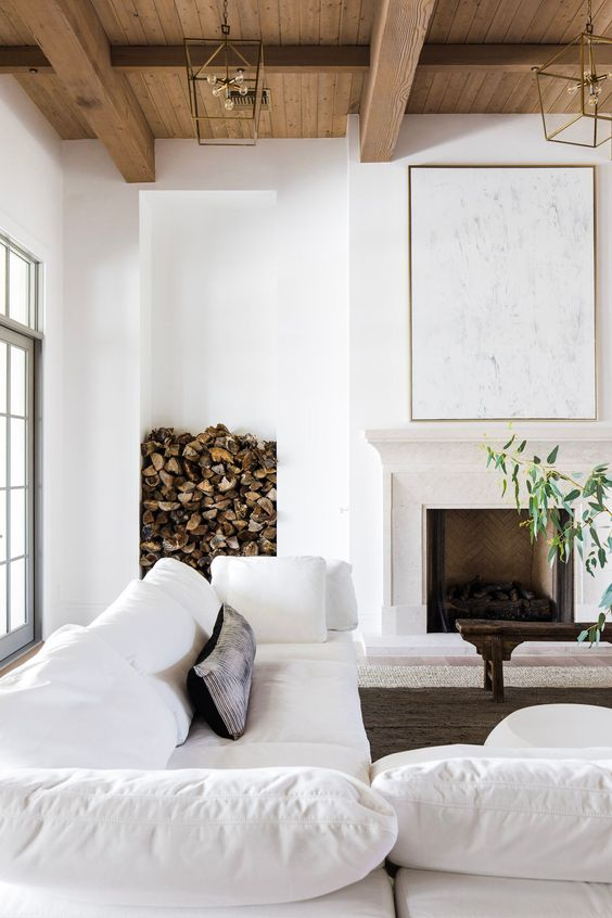 a modern farmhouse living room with a fireplace, white sofas, a firewood storage space, pendant lamps and a wooden bench