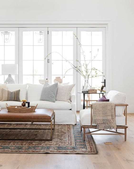a modern farmhouse living room with a white sofa, a white chair, a leather ottoman, a boho rug and a round table plus printed pillows