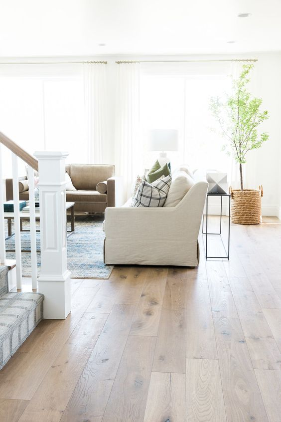a modern farmhouse living room with creamy walls and a neutral vinyl floor, white and taupe furniture, a potted tree in a basket