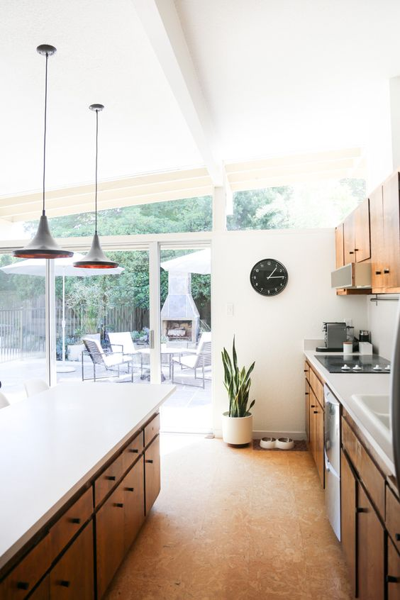 a modern kitchen with white walls, a glazed one, a cork floor, stained wooden cabinetry and pendant lamps is amazing