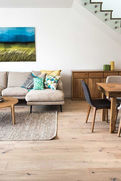 a modern living room with white walls and laminate flooring, a grey sectional, wooden furniture, a rug and a bold artwork
