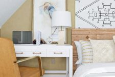a modern neutral bedroom with tan walls, white and tan furniture, a watercolor artwork and a chic desk is amazing
