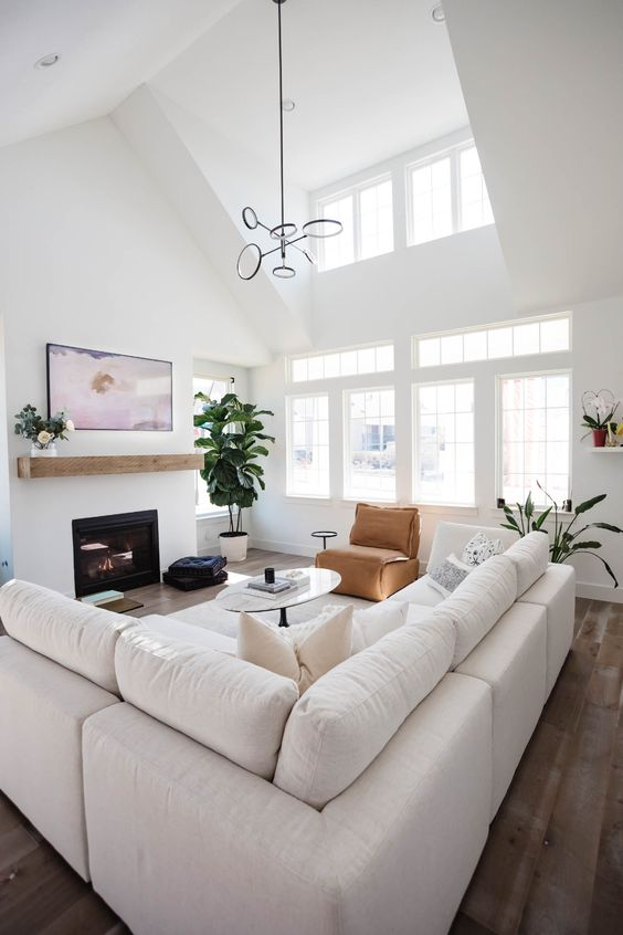 a modern neutral living room with a large white sofa, a fireplace with a mantel, a leather chair and a table, a pendant lamp