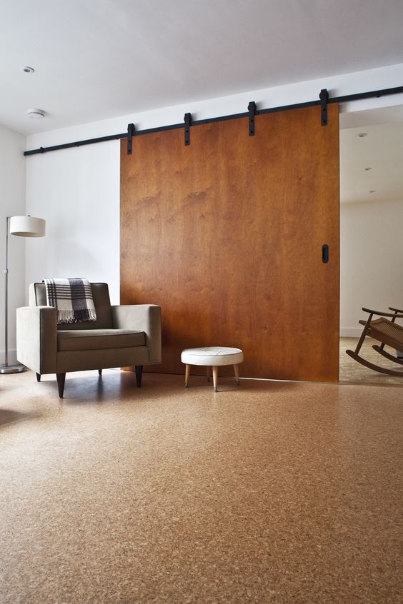 a modern space with white walls, cork flooring, a modenr chair and a stool, a sliding barn door is chic