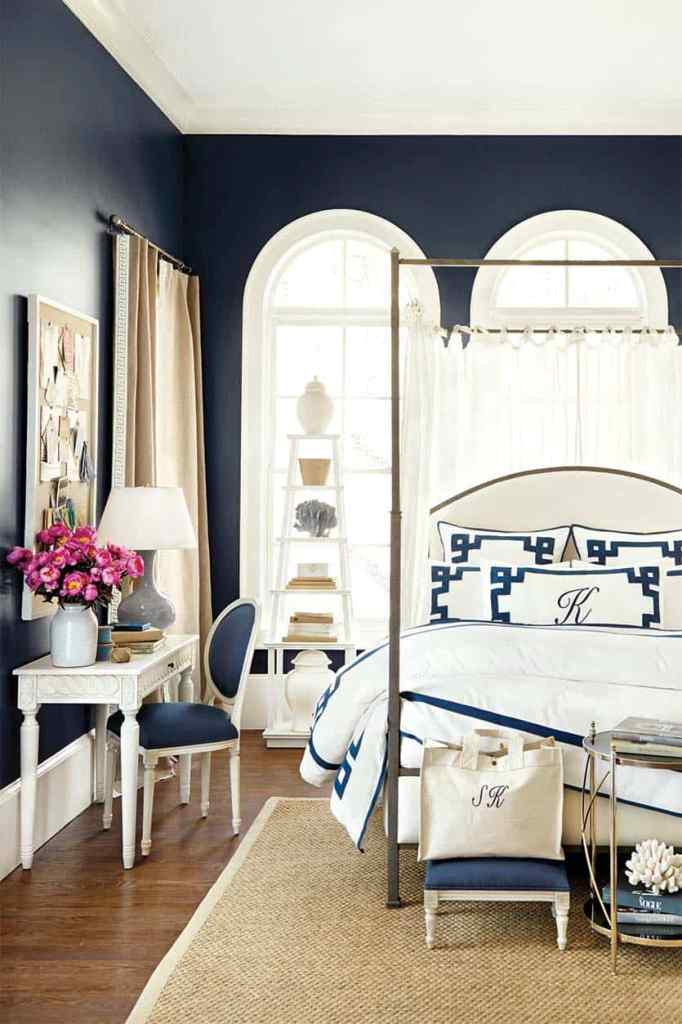 a nautical bedroom with navy walls, chic vintage furniture, bold navy and white bedding, a lovely ladder shelving unit and a memo board