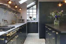 a navy attic kitchen with elegant gold touches, sconces and pendant lamps and lots of skylights to brign more light in