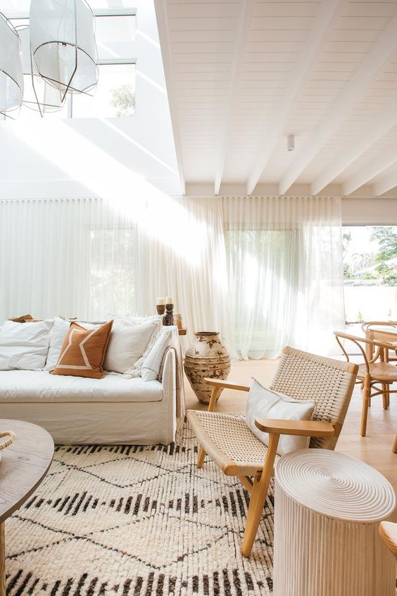 a neutral and chic living room with a white sofa, a woven chair, wooden tables, pendant lamps and a printed rug is cool