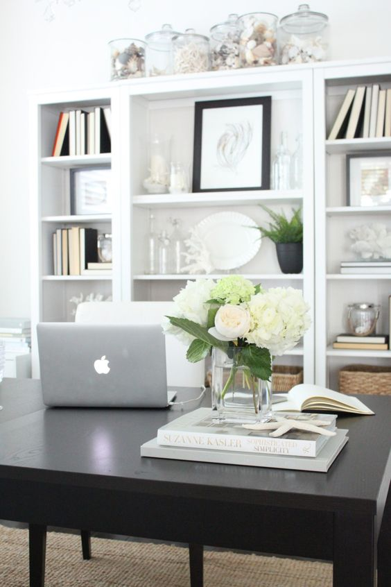 a neutral and classic coastal home office with a large storage unit, a black desk, a white chair, lots of jars with seashells