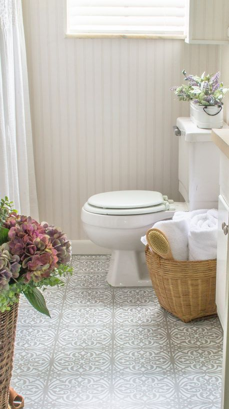 a neutral bathroom with white planked walls, a grey printed vinyl floor, white furniture and appliances and some blooms
