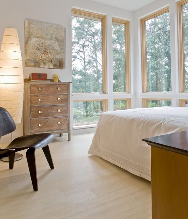 a neutral bedroom with neutral bamboo flooring, stylish mid-century modern furniture and a shabby chic dresser and glazed walls