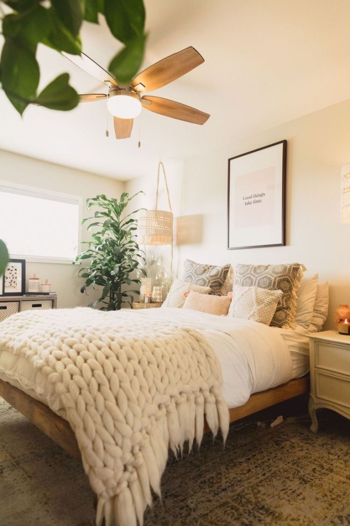 a neutral boho summer bedroom with wooden furniture, printed and knit and crochet bedding, a macrame lamp and lots of greenery