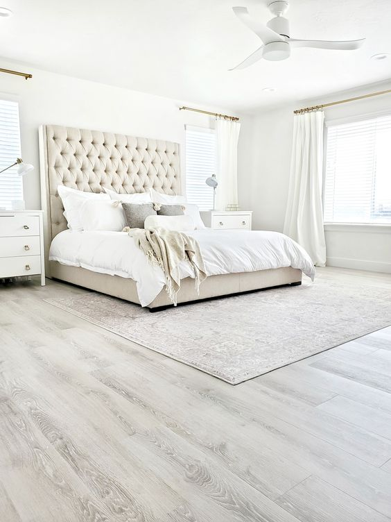 a neutral farmhouse bedroom with a grey vinyl floor, an upholstered bed with a statement headboard, white nightstands and some neutral textiles