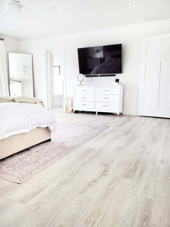 a neutral farmhouse bedroom with a grey vinyl floor, white walls, neutral furniture, a floor mirror and touches of brass