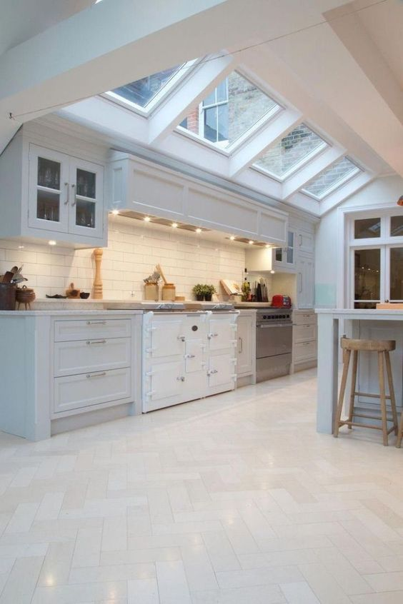 a neutral farmhouse kitchen with skylights, neutral herringbone tiles on the floor and white subway tiles on the backsplash is very airy