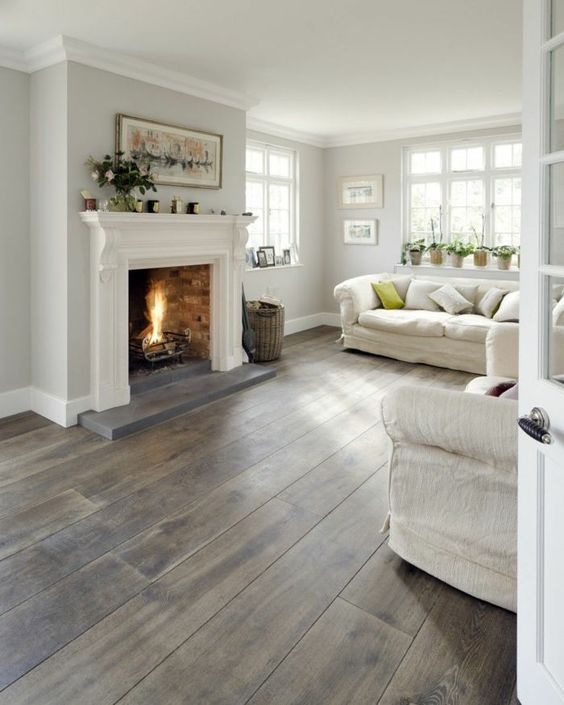 a neutral farmhouse living room with a fireplace, neutral furniture, a basket and potted plants is a very welcoming space