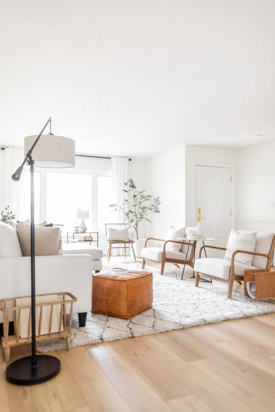 a neutral farmhouse living room with white walls and a very natural-looking vinyl floor, white furniture, leather ottomans and lovely lamps