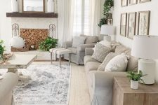 a neutral farmhouse summer living room with grey furniture and layered rugs, a non-working fireplace, a gallery wall and lots of greenery