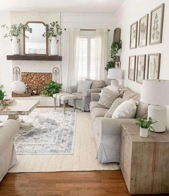 a neutral farmhouse summer living room with grey furniture and layered rugs, a non working fireplace, a gallery wall and lots of greenery