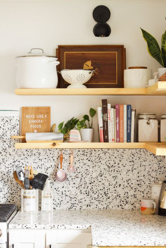 a neutral kitchen with a white terrazzo backsplash and countertops, wooden shelves and potted plants here and there