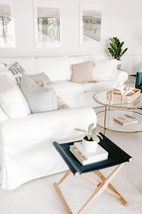 a neutral living room with a white Ektorp sofa, a navy stool, a round tiered coffee table and a gallery wall with family vacation pics