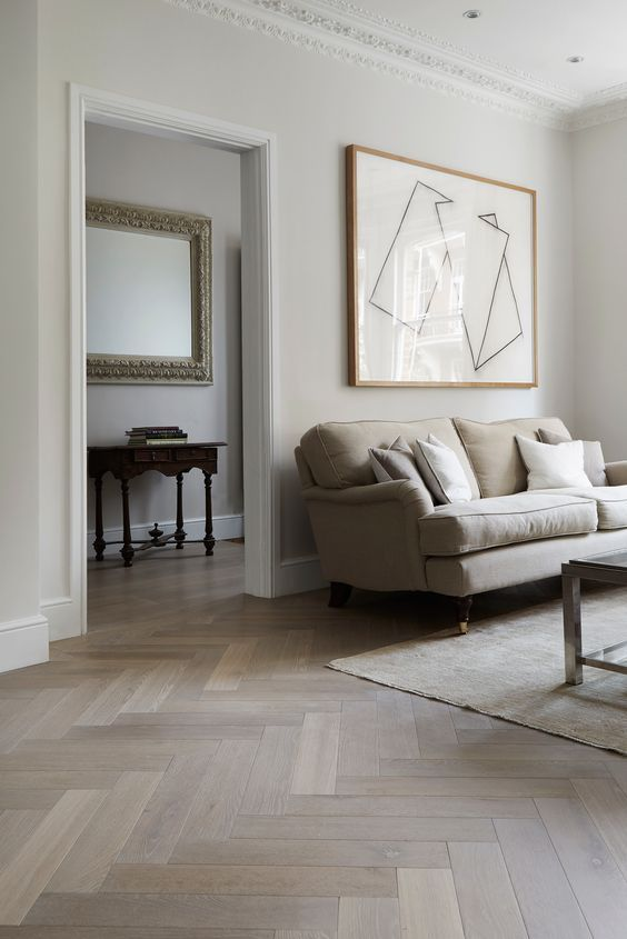a neutral living room with off-white walls and light stained parquet flooring, neutral furniture and an abstract artwork