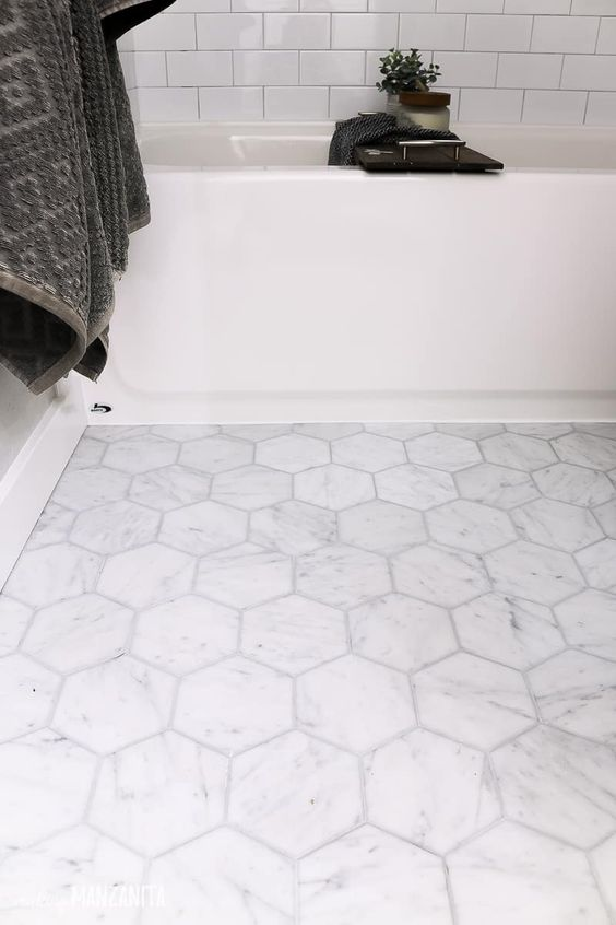 a neutral modern bathroom with subway tiles and a marble hex tile floor, a neutral bathtub and dark textiles is a very chic idea