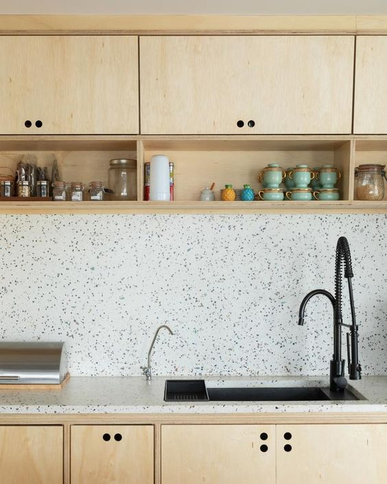 a neutral plywood kitchen with a white terrazzo backsplash and countertops plus black fixtures for a more modern feel
