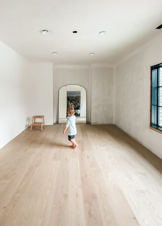 a neutral space with white and greyish walls, a neutral laminate floor and nothing else is very airy and feels light