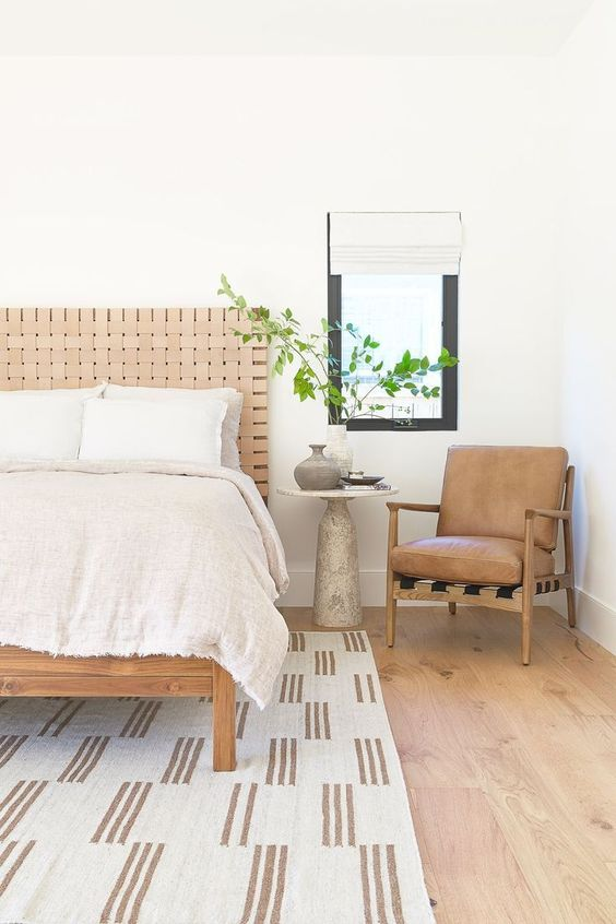 a neutral summer bedroom with a wooden bed with a leather headboard and a leather chair, neutral textiles and greenery in a vase