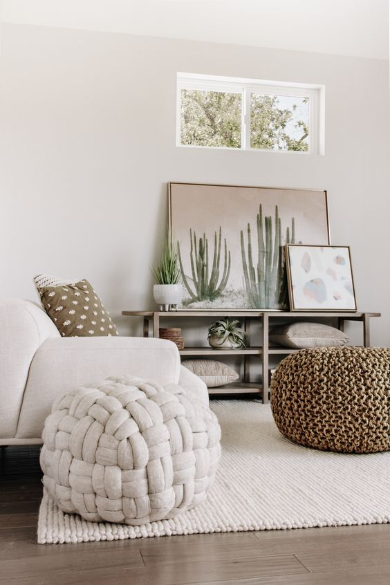 a neutral summer living room with a chair, woven poufs, an open shelving unit with artworks is a chic idea