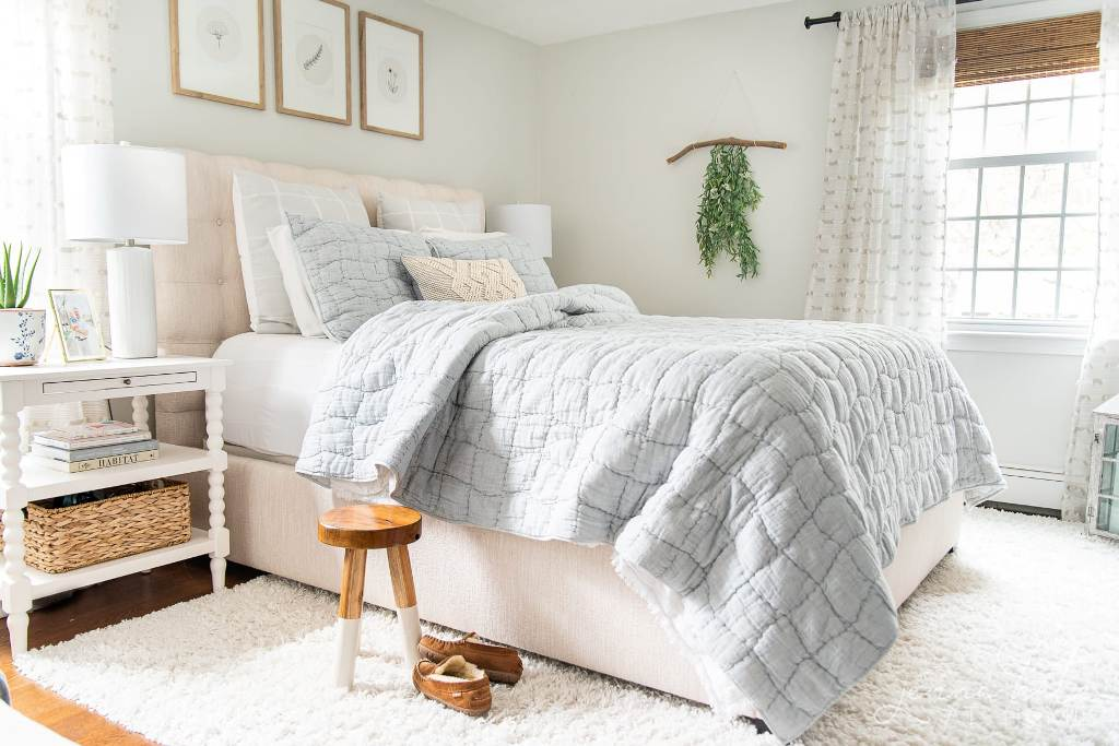 a neutral summer sleeping space with an upholstered bed, blue bedding, white nightstands, a gallery wall and greenery