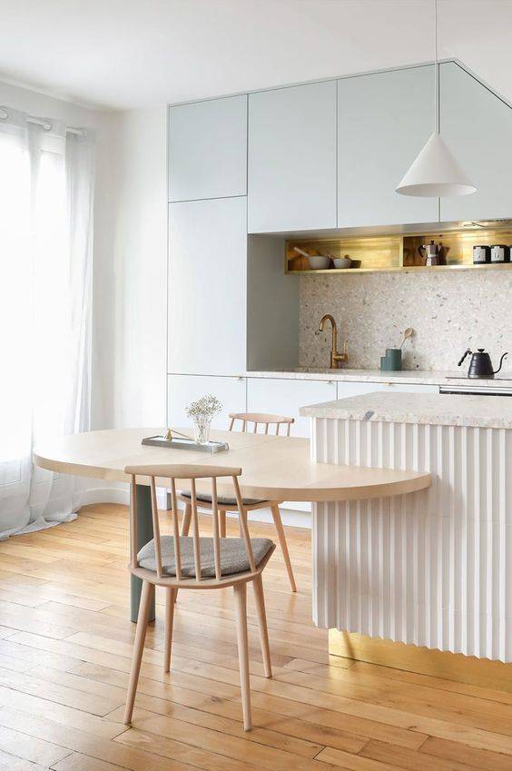 a pale blue kitchen with a grey terrazzo backsplash and countertops, a pretty kitchen island and a catchy built-in table
