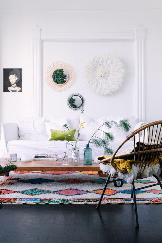 a pretty and lively living room with a white sofa, a bright printed rug, a rattan chair, a low coffee table and a gallery wall