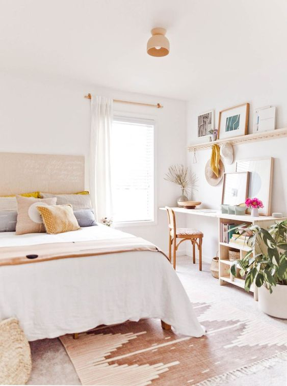 a pretty neutral bedroom with a large bed, a desk and a chair by the window, an open shelf, potted plants and some artworks