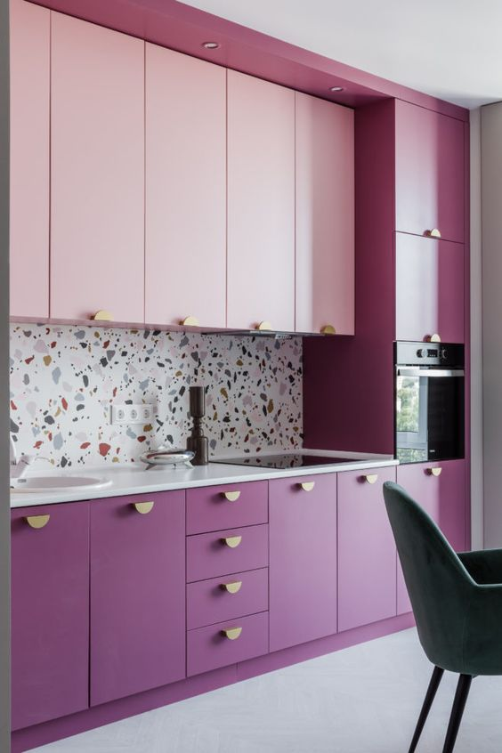 a purple and pink kitchen with gold knobs and a bright terrazzo backsplash plus white countertops for a balance
