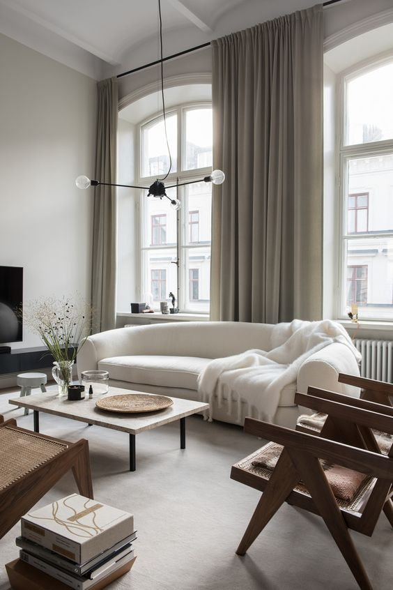 a refined Scandinavian living room with a curved white sofa, rattan chairs, a low coffee table, a pendant lamp and books