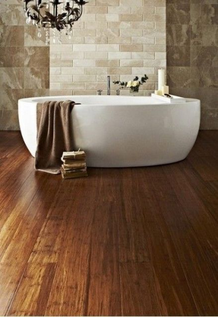 a refined bathroom with stone-looking tiles and bamboo flooring, an oval tub and a chic crystal chandelier is wow