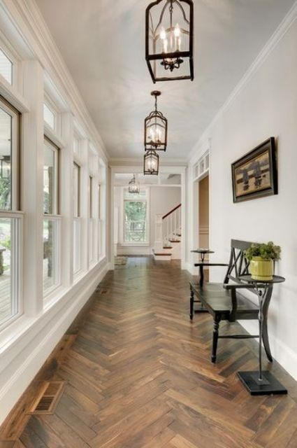 a refined entryway with dark parquet flooring, a black vintage bench, refined chandeliers and potted greenery
