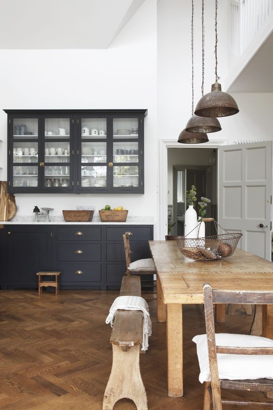 a refined kitchen black white walls and a rich stained parquet floor, black cabinets, metal pendant lamps and a rustic dining set