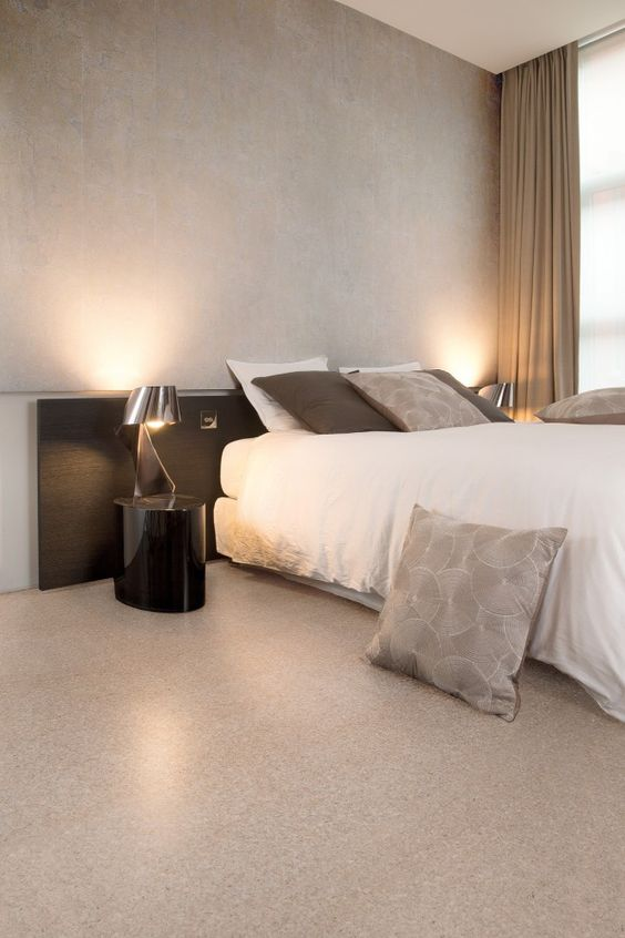 a refined minimalist bedroom with grey walls and a cork floor, chic and simple furniture and an eye-catchy nightstand and lamp