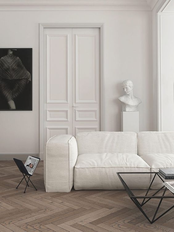 a refined minimalist living room with a white sofa, simple black tables, a statement artwork and a statuette is wow