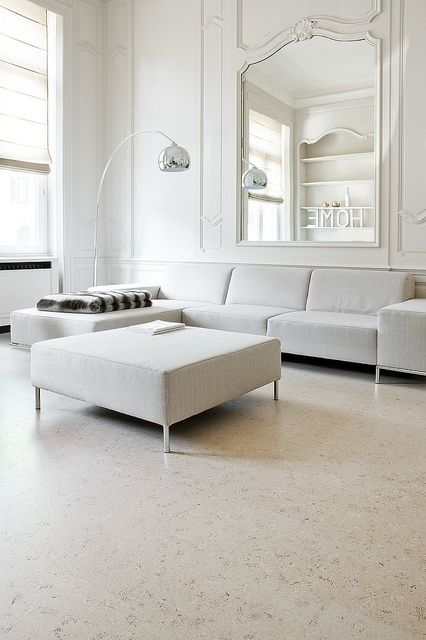 a refined minimalist living room with white paneled walls and a large mirror, white furniture and a whitewashed cork floor