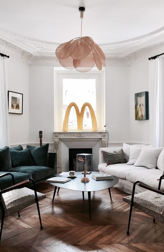 a refined modern living room with white walls, parquet floors, chic furniture, a non-working fireplace and a petal chandelier