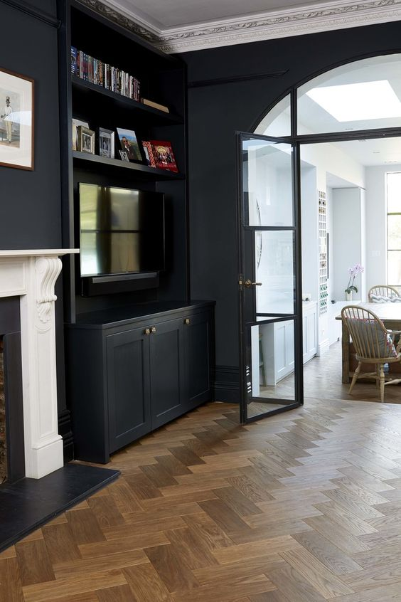 a refined moody space with a parquet floor, black walls and built-in cabinets plus a non-working fireplace