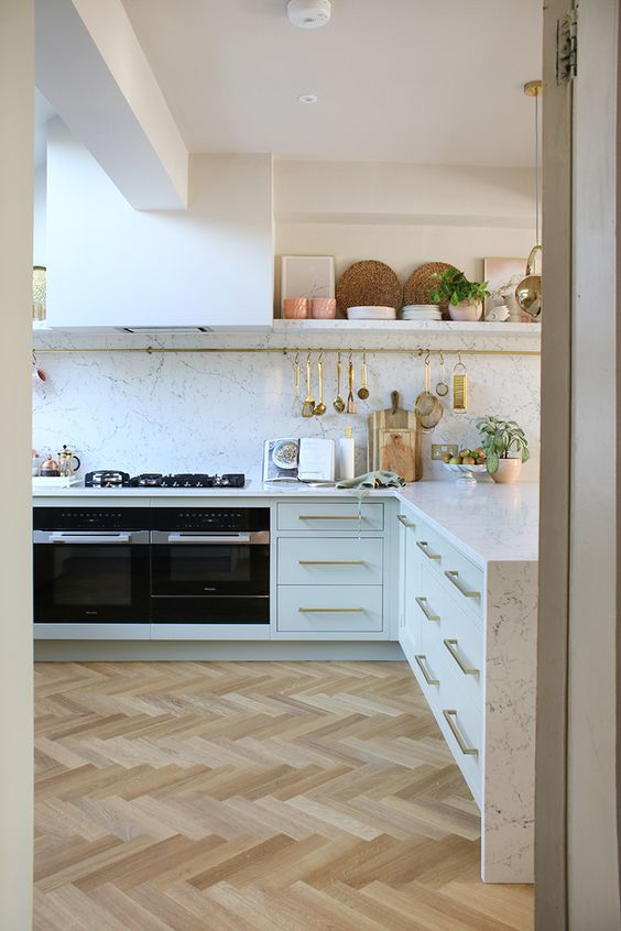 a refined neutral kitchen with a light parquet floor, white cabinets and a white stone countertop and a backsplash is cool