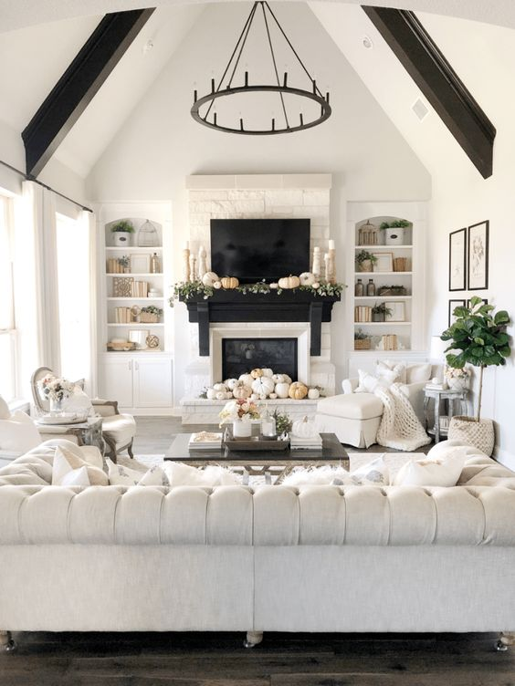 a refined neutral living room with a fireplace, a large and sophisticated tufted sofa, a chandelier, dark beams and white chairs