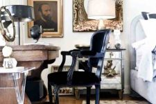 a refined vintage bedroom with a large bed, a mirror nightstand, a mirror in a chic frame, a carved wooden desk and a black chair